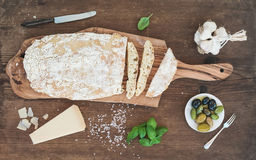 Freshly baked ciabatta bread with garlic, mediterranean olives, basil and Parmesan cheese on serving board over rustic Stock Photography