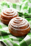 Freshly baked cinnamon buns on the green napkin Stock Photo