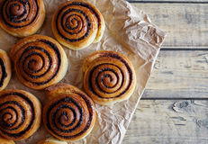 Freshly baked cinnamon rolls buns with cocoa and spices on parchment paper. Close-up. Top view. Kanelbulle. Royalty Free Stock Image