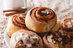 Freshly baked cinnamon rolls with icing and almonds macro. Horiz Royalty Free Stock Photography