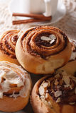 Freshly baked cinnamon rolls with icing and almonds macro. verti Stock Photos