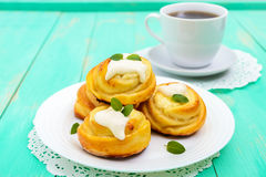 Freshly baked, cottage cheese buns, with cream and mint leaves and cup of tea. On a white plate on a light background Royalty Free Stock Image