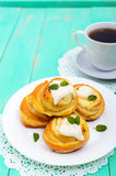 Freshly baked, cottage cheese buns, with cream and mint leaves and cup of tea on a white plate on a light background. Stock Photos