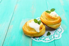 Freshly baked, cottage cheese buns, with cream and mint leaves on a white napkin Stock Images
