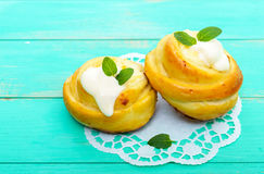 Freshly baked, cottage cheese buns, with cream and mint leaves on a white napkin. On a light background Royalty Free Stock Photography