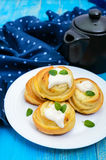 Freshly baked, cottage cheese buns, with cream and mint leaves on a white plate. On a blue background Stock Photos