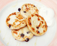 Freshly baked cottage cheese pancakes with raisin; with sour cre. Freshly baked cottage cheese pancakes with raisin and sour cream on white and pink plate Royalty Free Stock Photography