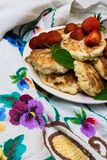 Freshly baked cottage cheese pancakes with raisins and strawberry, mint leaf.Frying process. Top view. Freshly baked cottage cheese pancakes with raisins stock images