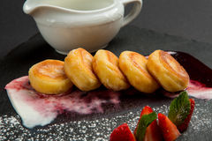 Freshly baked cottage cheese pancakes with strawberries and sour cream on dark plate. Stock Image