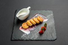 Freshly baked cottage cheese pancakes with strawberries and sour cream on dark plate. Stock Photos