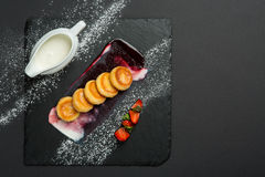 Freshly baked cottage cheese pancakes with strawberries and sour cream on dark plate. Stock Photo