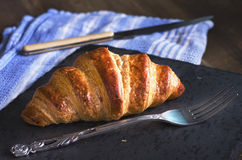 Freshly baked croissant on black stone. Blue kitchen towel on ba Royalty Free Stock Photos