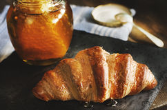 Freshly baked croissant on black stone. Honey and blue kitchen t Stock Image