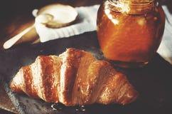 Freshly baked croissant on black stone. Honey and blue kitchen t. Owel on background Stock Photography