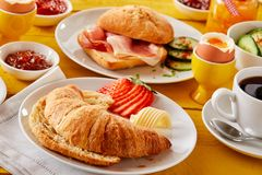 Freshly baked croissant with butter and strawberry. Served with a bacon roll, boiled egg, coffee and jellies or jams for a delicious spring breakfast Royalty Free Stock Images