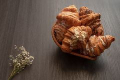 Freshly baked croissants with almonds, chocolate and powdered sugar  on a wooden dark table top view stock image