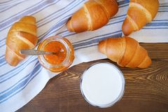 Freshly baked croissants, apricot or peach jam, on a striped linen towel on a wooden table. Next to a glass of milk. The concept stock images