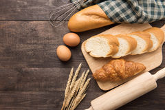 Freshly baked croissants, baguette and eggs on wooden background Stock Image