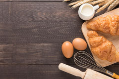 Freshly baked croissants, milk and eggs on wooden background Stock Photography