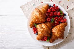 Freshly baked croissants with raspberries, blueberries and curra Royalty Free Stock Photo