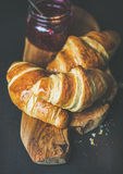 Freshly baked croissants with raspberry jam in jar. Breakfast concept. Freshly baked croissants with raspberry jam in jar on rustic wooden board over dark Royalty Free Stock Image