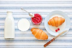 Freshly baked croissants, raspberry jam, milk in a bottle and in a glass, a knife on a linen towel. The concept of healthy eating stock images