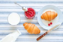 Freshly baked croissants, raspberry jam, milk in a bottle and in a glass, a knife on a linen towel. The concept of healthy eating stock photo
