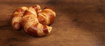 Freshly baked croissants on wooden cutting board, close-up.  stock photos