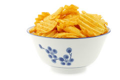 Freshly baked deep ridged potato chips. In a decorated ceramic bowl on a white background Royalty Free Stock Image