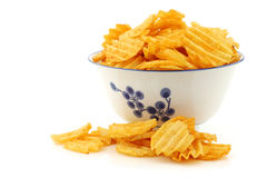 Freshly baked deep ridged potato chips. In a decorated ceramic bowl on a white background Royalty Free Stock Photos