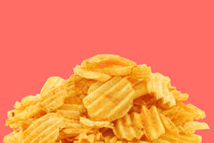 Freshly baked deep ridged potato chips. On a pink background Royalty Free Stock Images