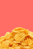 Freshly baked deep ridged potato chips. On a pink background Royalty Free Stock Photos