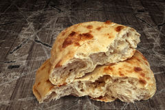 Freshly Baked Domestic Pitta Bread Loaf Torn Halves Set On Old Weathered Cracked Flaky Wooden Garden Table Stock Photography