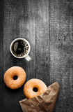 Freshly baked doughnuts with filter coffee. Freshly baked sugared ring doughnuts with a mug of full roast filter coffee and brown paper packaging on a grungy old stock photography