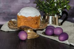 Freshly baked Easter cake on the kitchen table covered with icing and decorating topping with purple eggs. Easter holiday concept. stock photography