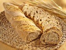 Freshly baked fitness bread on table. Freshly baked fitness bread and wheat on table royalty free stock photos