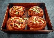 Freshly baked French raisin buns. Pains aux raisins on a vintage baking tray.  Stock Photos