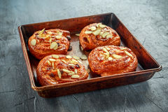Freshly baked French raisin buns. Pains aux raisins on a vintage baking tray.  Royalty Free Stock Photography