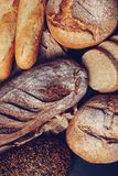 Flour and wheat with some handmade bread. - Image. Freshly baked handmade breads on the black royalty free stock photos