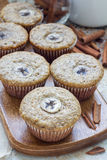 Freshly baked homemade banana cinnamon muffins with slice of banana on top, on wooden board Royalty Free Stock Photo