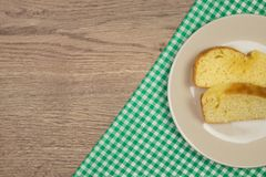 Freshly baked homemade cake slices and green checkered tableclot. H on wooden table. Top view with copy space Stock Photos