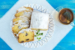 Freshly baked homemade cakes, decorating the top with powdered sugar, cut slices, with pieces of chocolate on a plate. And cup of tea on blue background. The Stock Images