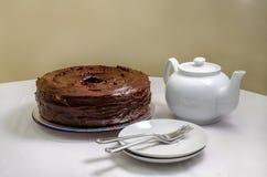 Freshly baked of homemade chocolate cake. Chocolate cake and white dishes on white background, closeup royalty free stock photo