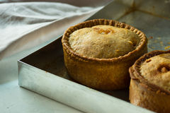 Freshly baked homemade pork pies with golden crust on aluminum baking tray, close up Stock Images