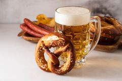 Freshly baked homemade soft pretzel with salt on white table with glass of beer. stock photography