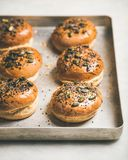 Freshly baked homemade buns with seeds for cooking burgers royalty free stock photography