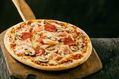 Freshly baked Italian pizza with ham and salami Royalty Free Stock Photos