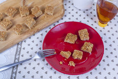 Freshly baked lapjacks covered in maple syrup. Freshly baked golden brown flapjacks covered in maple syrup on a red plate royalty free stock images