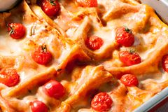 Lasagna with cherry tomatoes on top close-up food background Stock Images