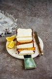Lemon cake dessert. Freshly baked lemon cake dessert with mascarpone cream over grey concrete table background close up - Image royalty free stock image